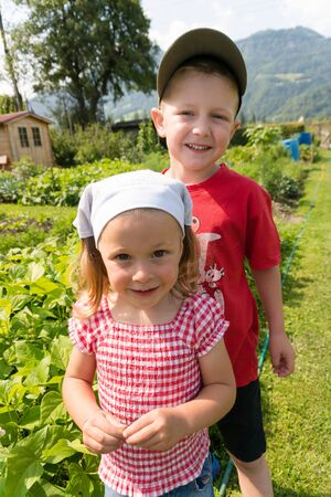 young girl and older borther proudly stad in in front of their vegetable patch in the Swiss countryside