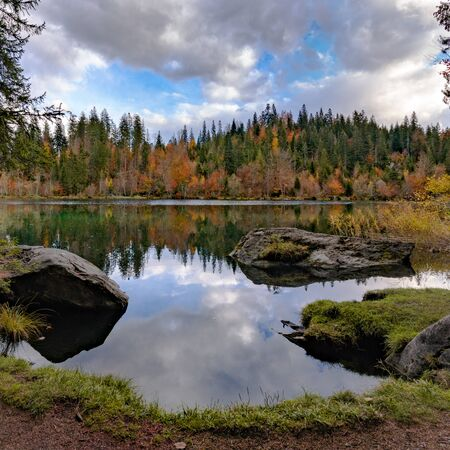 the picturesque Cresta Lake in the mountains of Switzerland near Flims in the Grisons on a beautiful fall day with colorful foliage and trees and reflections Stockfoto