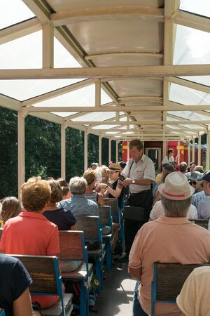 Arosa, GR / Switzerland - 24. July, 2019: tourists enjoy traveling in the open panorama carriage to Arosa with the ticket inspector checking tickets