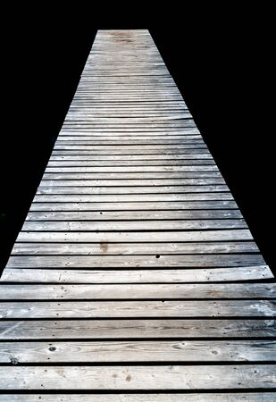 vertical view of a long wooden pier leading out into dark black peat lake water Stockfoto