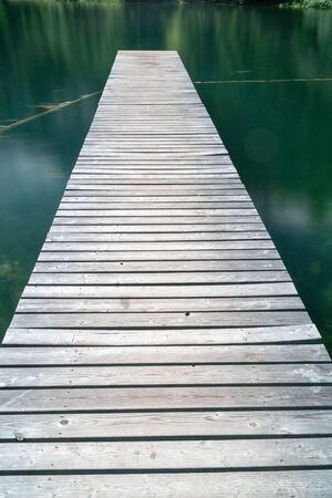 vertical view of a long wooden pier leads out into a mountain lake in Arosa Stockfoto