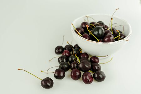 horizontal view of fresh organic ripe black cherries in a bowl and spread around on an isolated white background