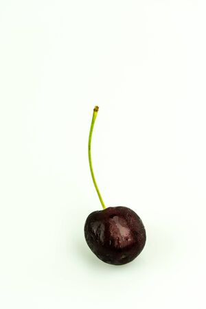 vertical view of a fresh organic ripe black cherry isolated on white background