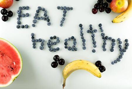 horizontal view of colorful healthy fruit and berries with text Stockfoto