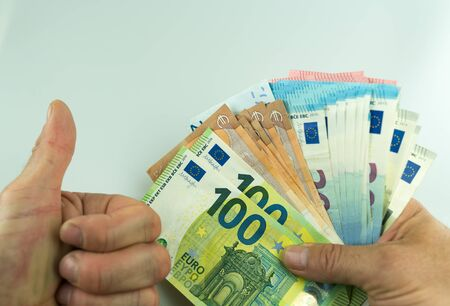 horizontal close up of male hands giving thumbs up and holding a large amount of Euro cash winnings