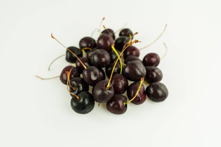 horizontal view of pile of fresh organic ripe black cherries isolated on white background