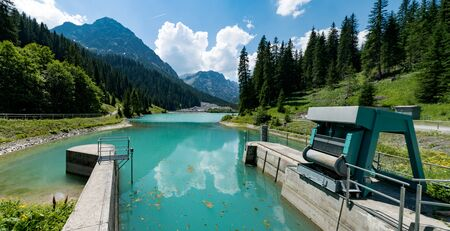 locks and weir of a dam on a turquoise colored mountain lake water reservoir in the Swiss Alps