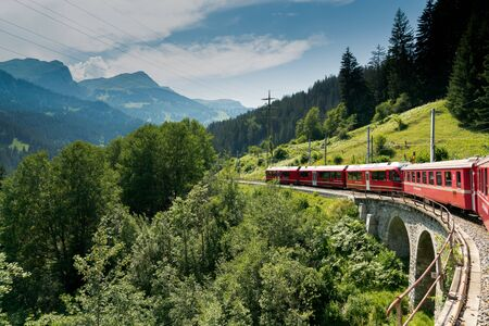 St. Peter, GR  Switzerland - 24. July, 2019: red narrow gauge train crossing over a stone bridge on a curvy stretch of track in the Swiss Alps on the Chur - Arosa line Editöryel