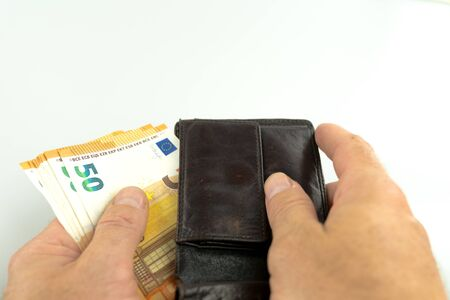 isolated view of a man taking fifty Euro banknotes out of a brown leather wallet Stockfoto