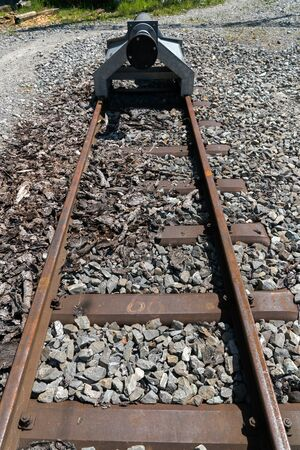 close up view of the end of narrow gauge railroad track with a buffer stop Stockfoto