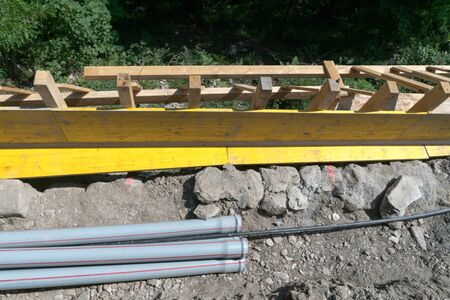 construction site with shawl panels and pipes ready for a concrete foundation along a railroad line with a steep drop to one side