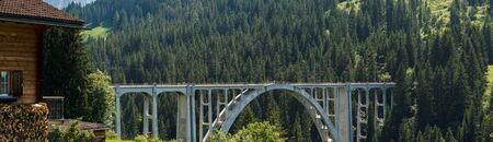 panorama view of the Langwies Viaduct in the mountains of Switzerland near Arosa with chalet in the foreground