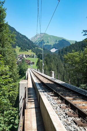 narrow gauge railroad tracks lead over the long bridge of the Langwies Viaduct in the Swiss Alps near Arosa