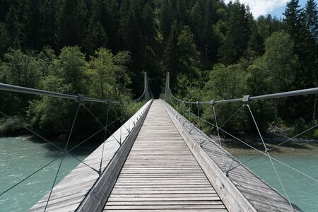 modern wooden suspension bridge over the river Rhine in the Ruinaulta Gorge in the Swiss Alps