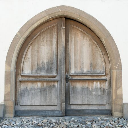 horizontal view of a massive winged wooden door in a stone wall with a wooden door arch Stockfoto