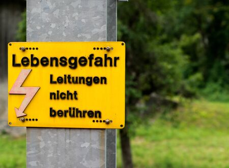 A yellow warning sign with German text reading