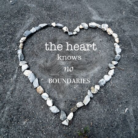 A heart made of colorful stones on sandy ground with the text the heart knows no boundaries Stockfoto