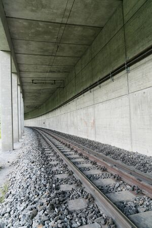 vertical view of the entrance of a tunnel for a narrow gauge train in the mountains of the Swiss Alps
