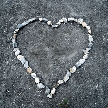 square view of a heart made of colorful stones on sandy ground Stockfoto