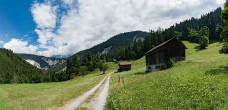 panorama mountain landscape with old wooden chalets and barns in summer in the Alps of Switzerland