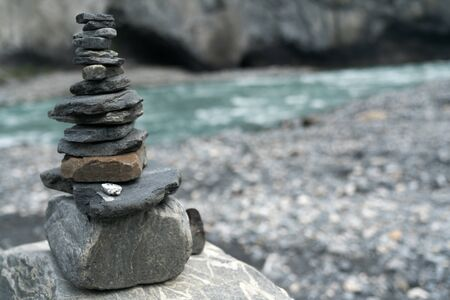 A rock cairn up close with a turquoise mountain river in the background
