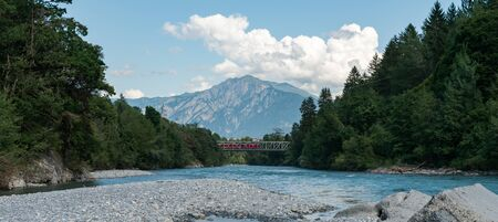A red train crosses a bridge over the river Rhine in the Swiss Alps