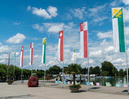 jorizontal view of flags and banners of Switzerland and Thurgau and Kreuzlingen in the harbor at Kreuzlingen