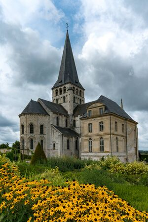 The historic Abbey of Saint George de Bocherville in Normandy with yellow flowers in the foreground and an expressive sky behind