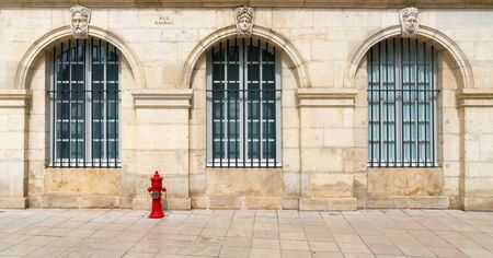 Close up view of stone house front with large grated windows of the art museum in Dijon with a red fire hydrant