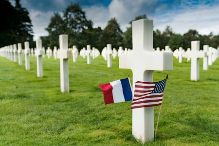 Selective focus view of view of cross headstones in the American Cemetery at Omaha Beach in Normandy with French and US flags 写真素材