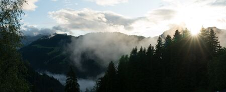 sun shining through fog and clouds after rain in a panorama forest and mountain landscape Фото со стока