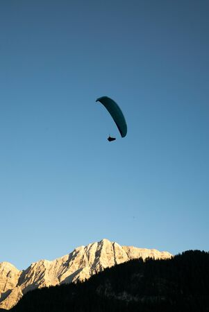 silhouette of paraglider in Dolomite mountain landscape in evening light near La Valle
