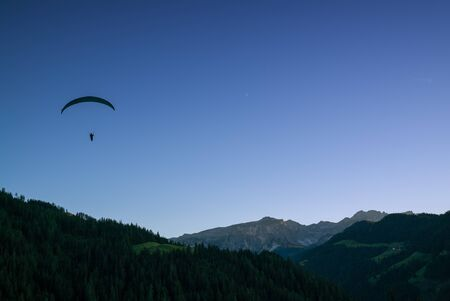 silhouette of paraglider in Dolomite mountain landscape at sunset near Wengen