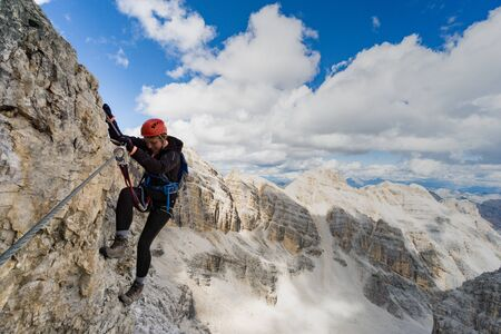 Horizontal view of attractive brunette female climber on a steep and exposed Via Ferrata in the Dolomites