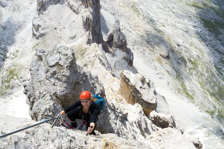 Horizontal view of an attractive blonde female climber on a steep Via Ferrata in the Italian Dolomites with a great view behind