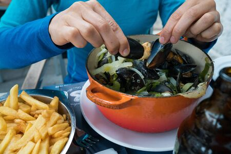 Horizontal view of hands of a woman eating traditional mussel and french fries dish called