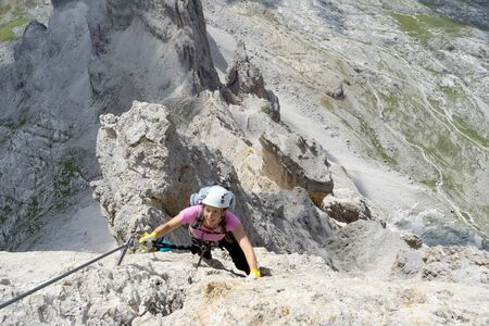 Horizontal view of a pretty female climber in lilac shirt on a steep Via Ferrata in the italian Dolomites with a great view behind
