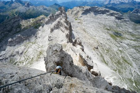Horizontal view of an attractive female climber on a steep Via Ferrata in the Italian Dolomites with a great view behind