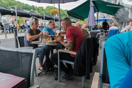 Dinant, Namur  Belgium - 11 August 2019: people dining out and eating traditional mussel and french fries dish Editorial