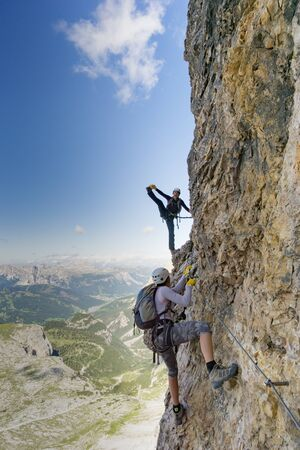 Vertical view of an attractive female climbers on a steep Via Ferrata in the Italian Dolomites with a great view behind and having fun