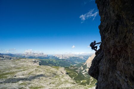 Horizontal view of an attractive female climber in silhouette on a steep Via Ferrata in the Italian Dolomites with a great view behind