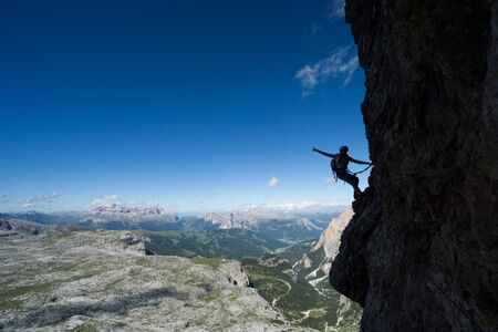Horizontal view of an attractive blonde female climber in silhouette on a steep Via Ferrata pointing to the sky