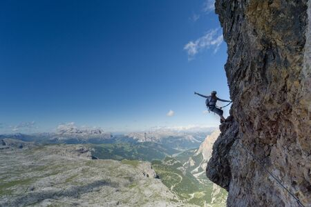Horizontal view of an attractive blonde female climber on a steep Via Ferrata pointing to the sky