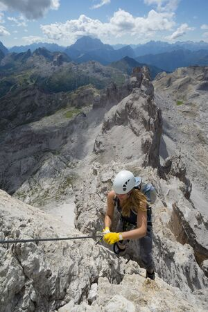 Vertical view of an attractive female climber on a steep Via Ferrata in the Italian Dolomites with a great view behind Stock fotó