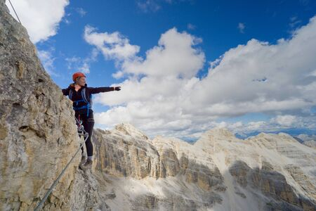 Horizontal view of attractive brunette female climber on a steep and exposed Via Ferrata in the Dolomites pointing to the distance