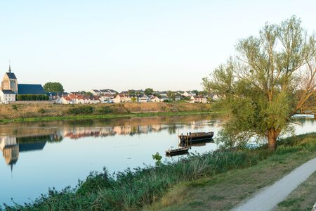 Horizontal view of the smalltown of Jargeau in the French countryside on the Loire river with riverboats in the foreground 写真素材