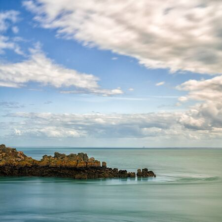 Square format view of a rocky cliff outcrop in a calm ocean under an expressive sky on the Emerald Coast in France
