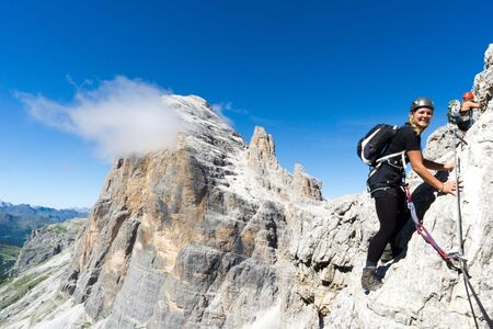 attractive blonde female mountain climber on a steep Via Ferrata in the South Tyrol