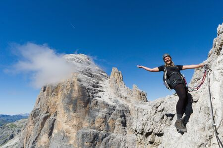 attractive blonde female mountain climber on a steep Via Ferrata in the South Tyrol waving and smiling