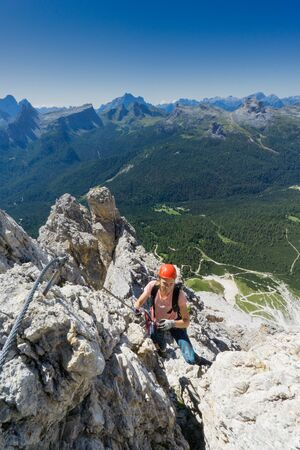 attractive brunette female mountain climber on a steep Via Ferrata in the South Tyrol